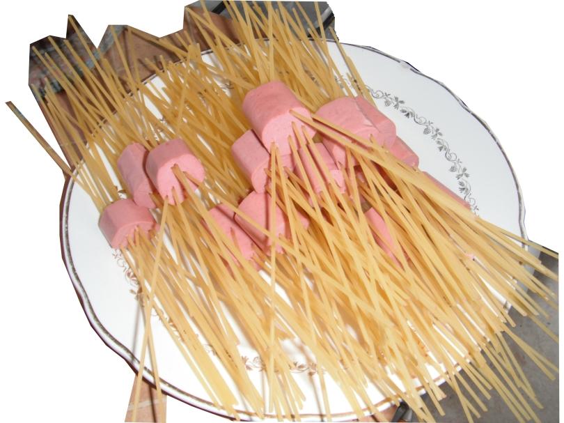 Insertar los espaguetis en los trozos de salchichas.