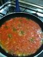 Sartén donde se está sofriendo tomate, cebolla y pimiento.